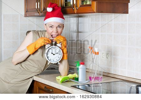 Young cleaning lady in the kitchen with vintage alarm clock