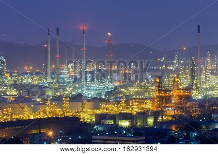 Oil refinery night lights with mountain background