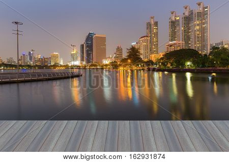 Opening wooden floor, City office building with reflection at twilight, Bangkok Thailand