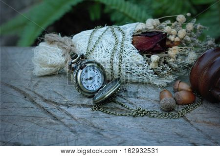 Antique pocket watch and hourglass with dried flowers