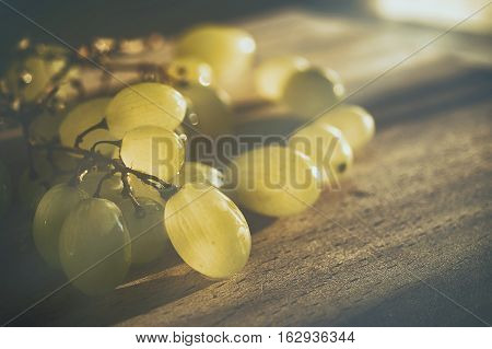 Summer grapes on a wooden board in a warm light.