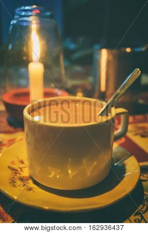 Candlelight dinner and traditional Indian hot drink - masala tea in romantic tropical cafe on the beach, Goa, India. Spiced tea with milk. Soft selective focus and blurred background