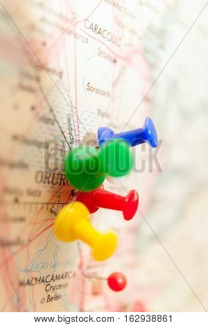 Travel destination points on a map indicated with colorful thumbtacks and shallow depth of field with space for copy