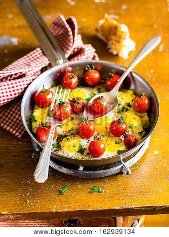 Fried quail eggs with cherry tomatoes, mozzarella cheese and chopped fresh curly parsley in a frying pan for breakfast, selective focus