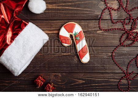 Santa's cane and hat with red beads on the brown wooden table, New Year concept