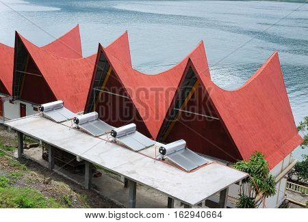 Solar Water Heater supply electricity to batak-style houses with red roofs, Lake Toba, Indonesia.