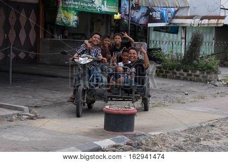 MEDAN, NORTH SUMATRA, INDONESIA - DECEMBER 18, 2016: Street Photography - Five children on the motorbike