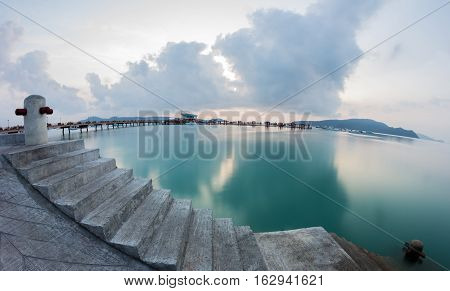 Stunning sunrise at industrial pier with torquise water and cloudy sky at the background.