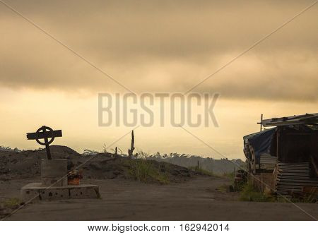 Grim atmospheric photo of road with cross on the side, near Merapi Volcano, Java, Indonesia