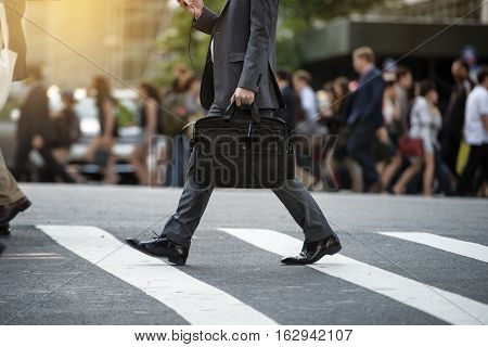 Businessman crossing the street on crosswalk and honding a laptop bag and smatphone in the city