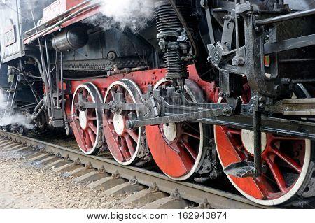 Wheels of black steam locomotive Er-794-12 on railway