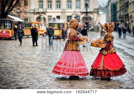 two woman in traditional clothes standing in the square in old city Lviv