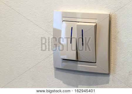 Modern white double light switch on the wall turn on or turn off the lights