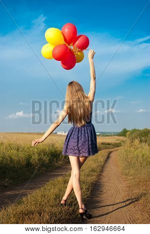 girl in short dress walking along a country road with the balloons in his hands