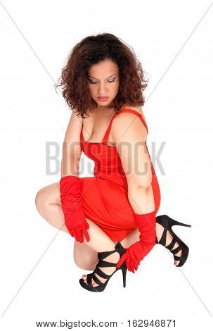 A beautiful young woman in a red dress and red cloves kneeling on the floor fixing her high heels isolated for white background.