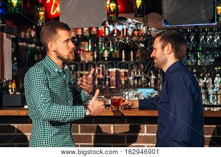 two young man talking at counter. two friends standng in bar and drinking whisky, Two confident young men in shirt and tie talking to each other and gesturing while drinking whisky at the bar counter
