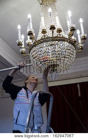 A Woman Worker Looks Like The Dust From The Chandeliers