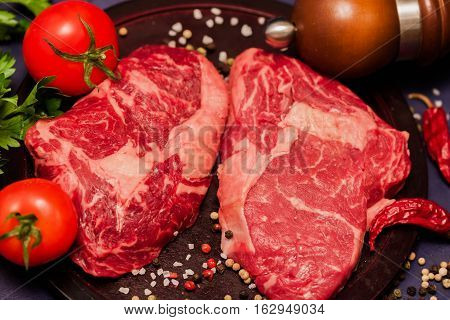 Marmara meat has a delicate taste and It contains ingredients that prevent the formation of Bad cholesterol. Raw juicy steaks from marble beef with seasonings on dark wooden background.