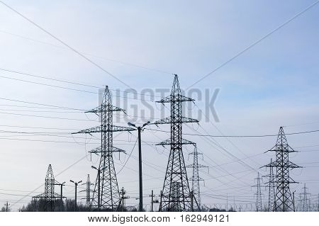 Several metal electricity pylon in the field. Cloud blue sky slight haze. The supports holding the wire. Visible tops of the trees.