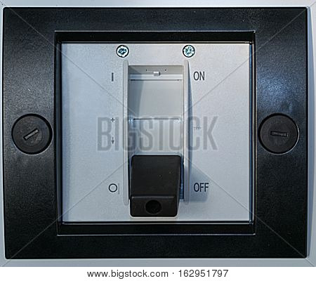 Electric circuit breaker on the front panel of the electrical Cabinet. Around him a black plastic frame for protection and beauty.