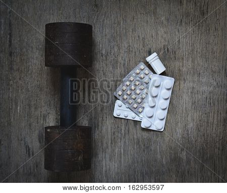 the old dumbbell on a wooden background with anabolic pills dirty sport abstract