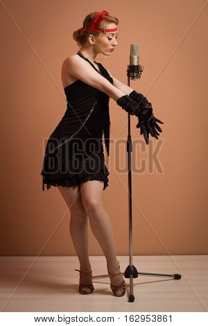 Pretty Actress In Black Retro Dress Singing With Microphone