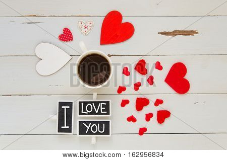 St Valentine's Day vintage overhead composition with I love you confession, hearts and coffe mug on wooden background