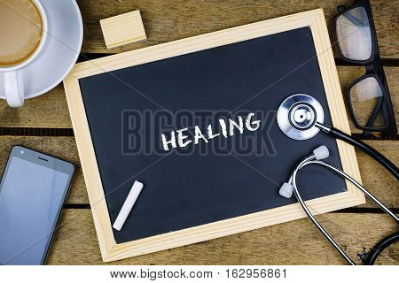 Medical Conceptual. Top view of mobile phone, hot coffee, eye glasses, stethoscope and blackboard written with medical terminology on wooden background.