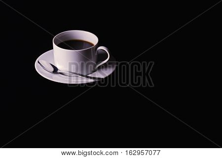 An image of a cup of black coffee with saucer and spoon shot on a black table top lighting from the left.