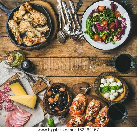 Party table arrangement. Rustic table set with salad, olives, chicken, tomato, feta cheese brushettas, snacks and red wine, top view, copy space. Slow food, banquet, catering concept, square crop