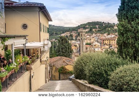 Fiesole Florence Italy - Oct 9 2016. View of people dine in the restaurant and Fiesole town center with cathedral tower in the background