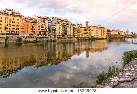 Houses and bridge on the Arno river with reflections