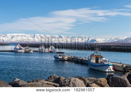 Fishing boats are docked at the pier in the harbor of Saudarkrokur. On the horizon are snow-covered mountains on the other side of the Skagafjordur fjord, Iceland