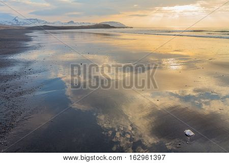 Waterline at Brimilsvellir beach with shells and reflections of a cloudy evening sky with orange colored sunbeams. In the background the snow-topped mountains of Snaefellsnes peninsula, Iceland