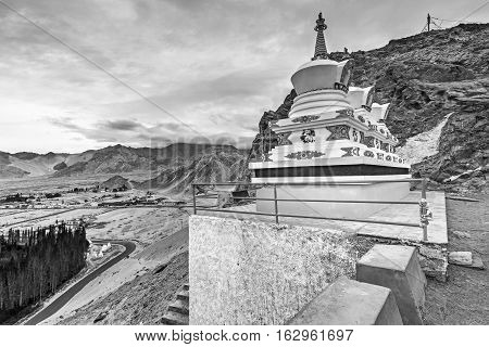 Thiksay monastery with view of Himalayan mountians and blue sky with white clouds in backgroundLadakhJammu and Kashmir India. Black and white image.