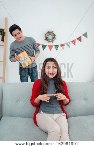 Christmas Asian Couple. A handsome man giving her girlfriend/wife a gift at home celebrating New Year People