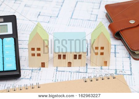 Wooden model of house on blueprints, construction plan