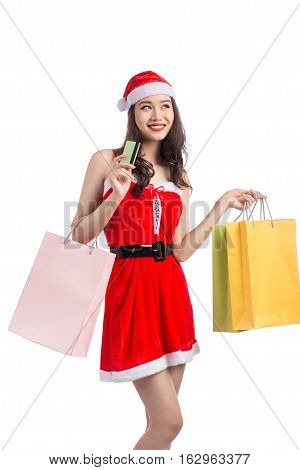 Smiling woman holding shopping bags before christmas showing credit card.
