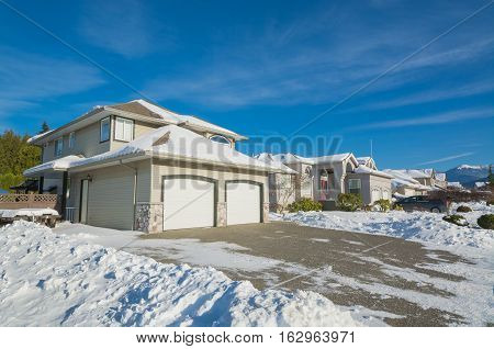 Double garage of big luxury house with driveway and front yard in snow. Street of residential houses on winter sunny day