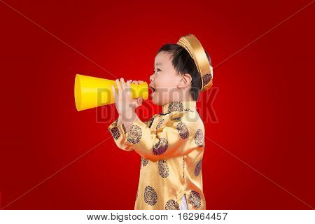 Portrait of a little asian boy wearing a traditional festival costume. Kid shouting through toy megaphone. Communication concept. Tet holiday