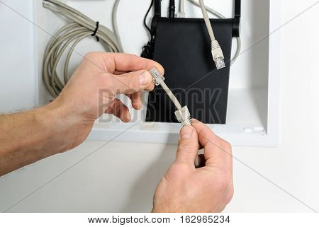 Connecting wi-fi router to the Internet. Human hand holding the cable and connector.