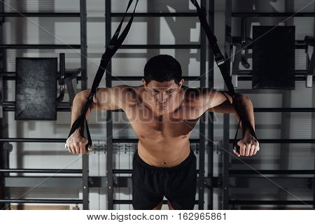 Attractive Man Does Crossfit Push Ups With Fitness Straps In The Gym's Studio.