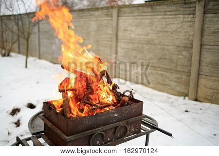 Barbecue In The Backyard In The Winter. Flames For Background.