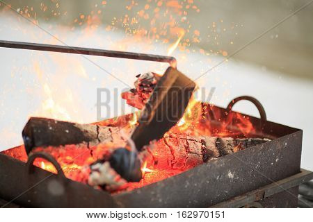 Hand With Poker Adjusts The Coals In The Brazier. Lighting The Barbecue In The Backyard In The Winte