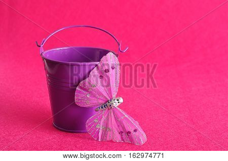 A metal bucket with a silk butterfly isolated against a pink background
