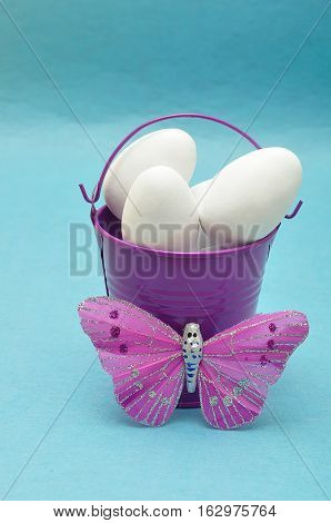 A purple metal bucket filled with white easter eggs displayed with a silk butterfly against a blue background