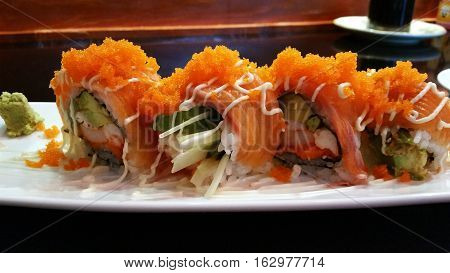 Tobiko rolls on the white plate, ready to serve.