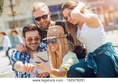 Group of friends taking a selfie with smartphone