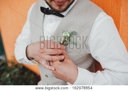 groom bow tie and waistcoat holding boutonniere