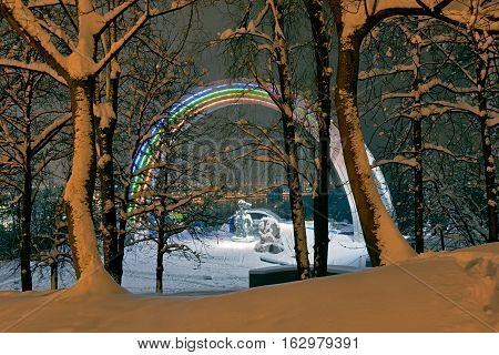 Winter season in Kiev. Illuminated Friendship Arch and Dnepr river through snowy trees.